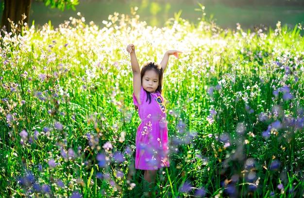 紋付き蛇甘い紫色の花の庭のフィールドで幸せな小さなアジアの女の子