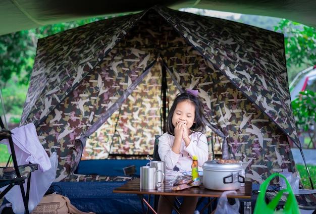 座っていると、キャンプに行きながらテントの前で朝食を食べる小さなアジアの女の子。屋外アクティビティや自然の中での冒険の概念