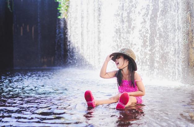 幸せな小さなアジアの女の子は、休日に滝を遊んで帽子を着用します。