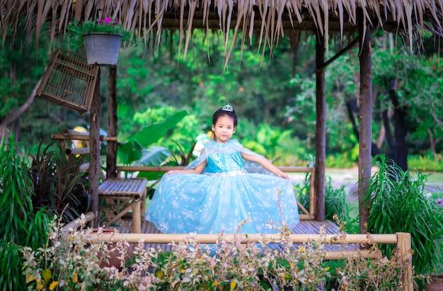 Портрет милой улыбающейся маленькой девочки в костюме принцессы, стоящей в хижине