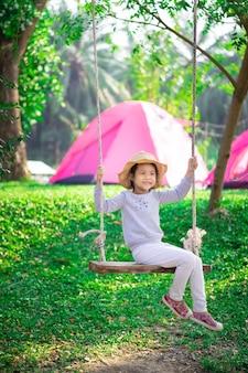 キャンプ中にブランコに座っているピンクのドレスの少女
