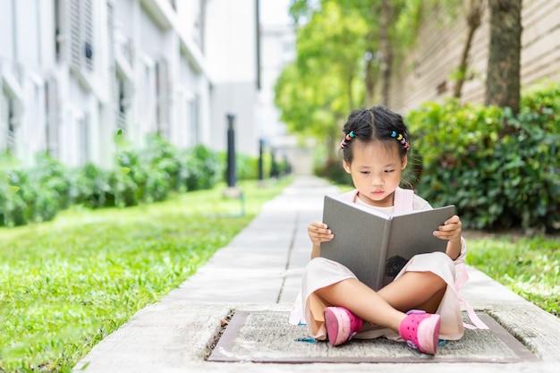 Маленькая девочка, читающая книгу с рюкзаком, сидящим в парке, готовым вернуться в школу