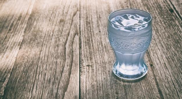 木の背景に水のガラス