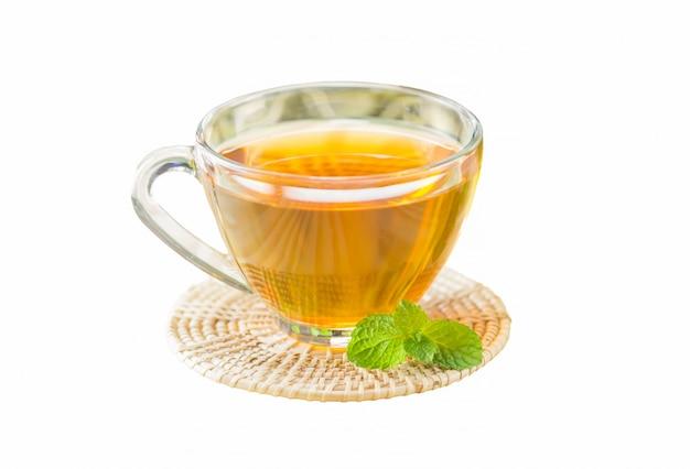 白い孤独な背景と木製の皿の上にお茶のカップ