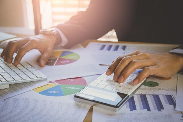 Бизнесмен или бухгалтер работает на калькулятор для расчета концепции бизнес-данных