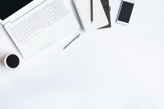 フラットに白いデスク事務所を置きます。デスクテーブルの上に不可欠な要素の平面図です。