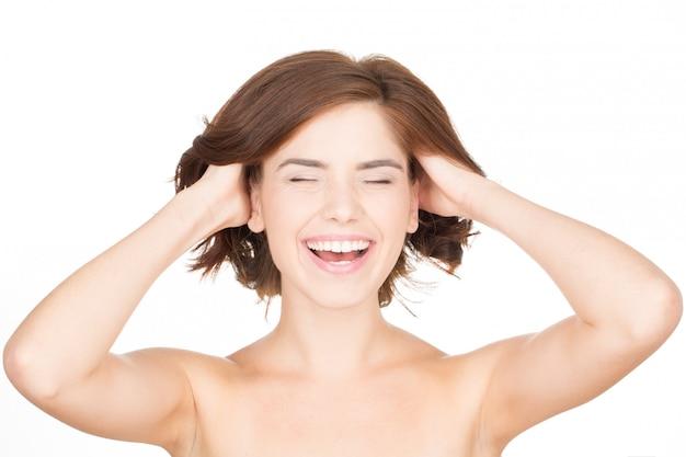 Почувствуй свежесть. горизонтальный портрет молодой женщины смеясь и касаясь ее волосам