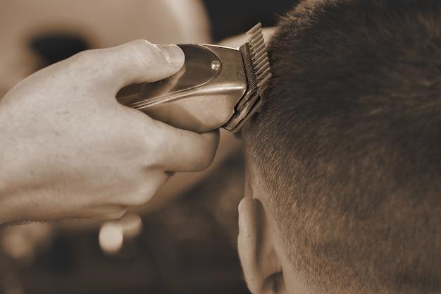 それがトリマーの目的です。男性クライアントに散髪をしながらトリマーを使用して床屋のクローズアップショット