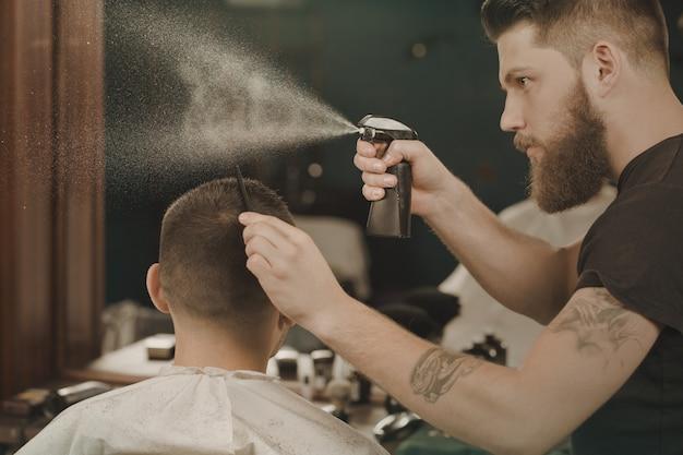 髪にスプレー。クライアントの髪に水を噴霧する理容室の肖像画