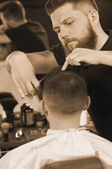 プロの髪をスタイリングします。プロのはさみを使用して彼の男性のクライアントに散髪を与えるハンサムなひげを生やした床屋の垂直ショット