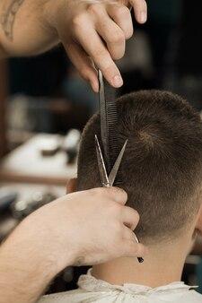 理髪店で髪を切る。理髪店で散髪を得る男のクローズアップショットをトリミング
