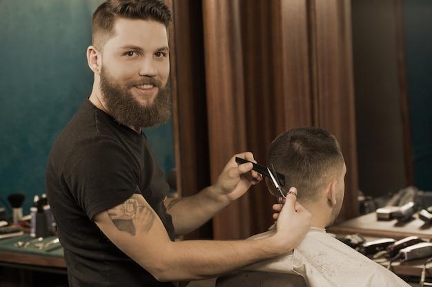 プロの床屋をスパイします。地元の理髪店で男性クライアントに散髪をしながら、カメラに喜んで笑っているハンサムな刺青理容室