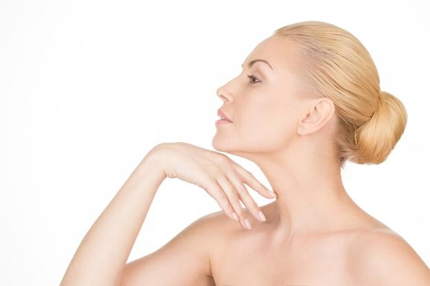 優雅に老化する。彼女の首に触れる美しい成熟した女性のクローズアップのプロフィール
