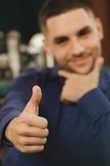 Он любит свою бороду. выборочный фокус на руке клиента парикмахерской показывает палец вверх жест