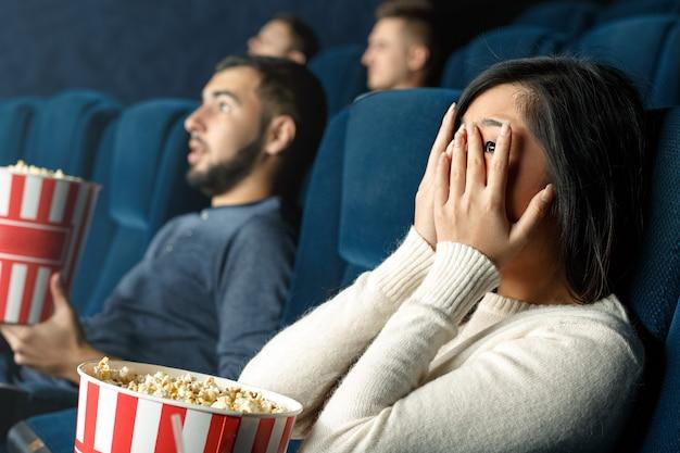 ホラー映画は勇敢な映画です。映画館で怖い映画を見ている彼女の手で彼女の目を閉じて怖い女の子のクローズアップショット