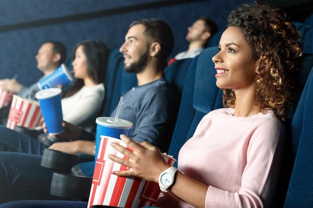 休みの日を過ごすのに最適な方法。地元の映画館で映画を元気に楽しんで笑っている美しいアフリカ女性の水平方向の肖像画