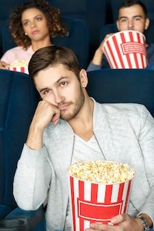 非常に退屈。ポップコーンを保持している映画館で映画を見て退屈探している若い男の垂直ショット