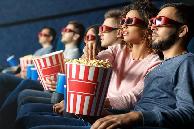 素晴らしい映画を楽しんでいます。飲み物を飲んでポップコーンを食べて映画を見ている友人のグループのショット