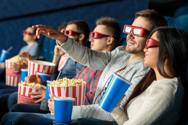 あなたはそれを見ましたか?彼の女性の友人に映画の画面で何かを見せて彼の手で指しているハンサムな若い男