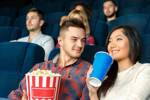 彼は彼女の笑顔を見るのが大好きです。彼女は映画館で映画を見て彼女の飲み物を楽しんでいる間彼のガールフレンドを暖かく見て若いハンサムな男