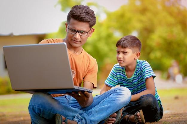 Два индийских брата работают на ноутбуке