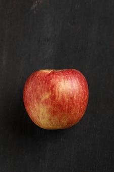 Свежее красное яблоко на темном фоне