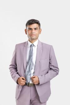 Молодой индийский мужчина в костюме и показывая другое выражение