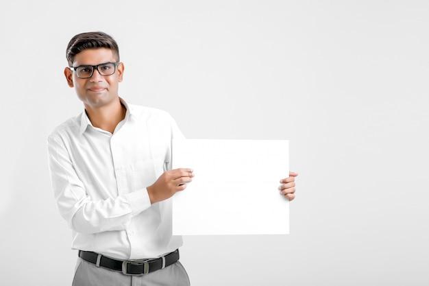 白い背景の上に空白の看板を示す若いインドビジネスエグゼクティブ