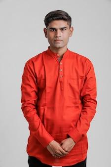 Индийский / азиатский мужчина в красной рубашке и стоя над белым