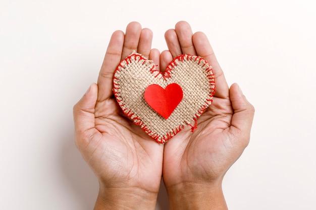 白い背景の上の手で小さな心。バレンタインの日の概念