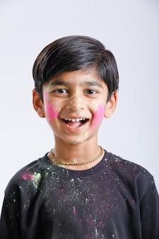 Индийский маленький мальчик играет с цветом и дает несколько выражений на фестивале холи