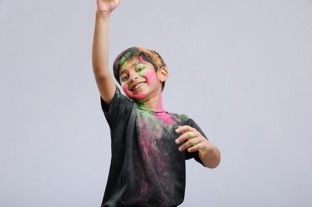 Индийский маленький мальчик играет с цветом в фестивале холи