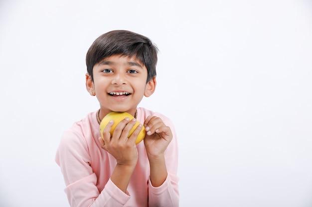 マンゴーを食べるインド/アジアの小さな男の子