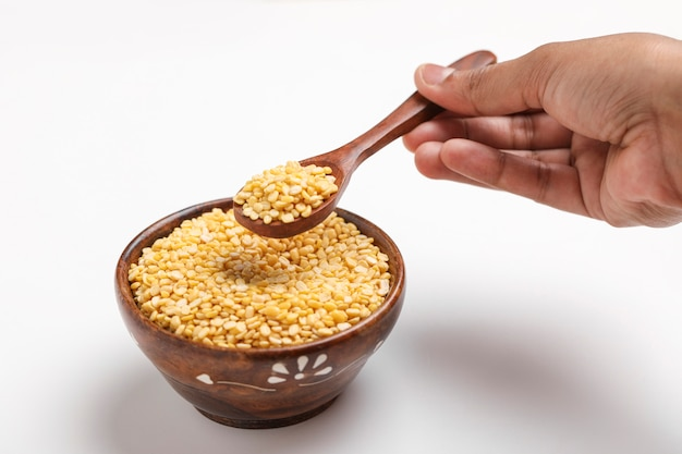 黄色のムングムングダルレンズ豆豆豆と白い背景の上のスプーンボウル