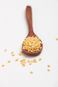 白い背景の上の木のスプーンで黄色のムングムングダルレンズ豆豆
