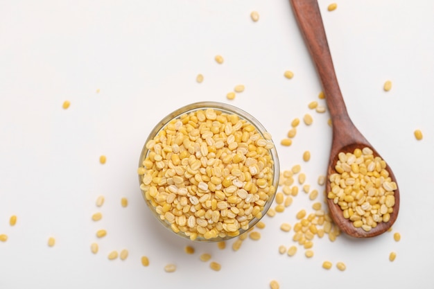 白い背景の上のガラスのボウルに黄色のムングムングダルレンズ豆豆
