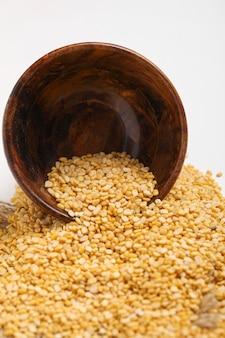 白い背景の上の木製のボウルに黄色のムングムングダルレンズ豆豆