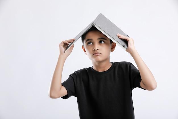Маленький индийский / азиатский мальчик с книгой на голове и серьезно думает