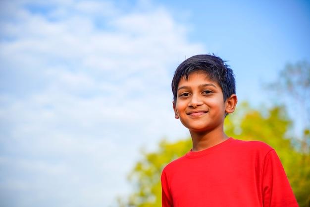 Счастливый индийский ребенок, играющий на земле