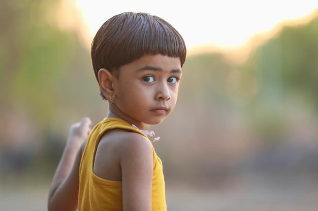 地面で遊んで幸せなインドの女児