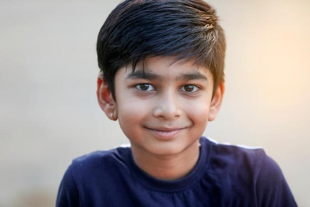 地面で遊んで幸せなインドの子