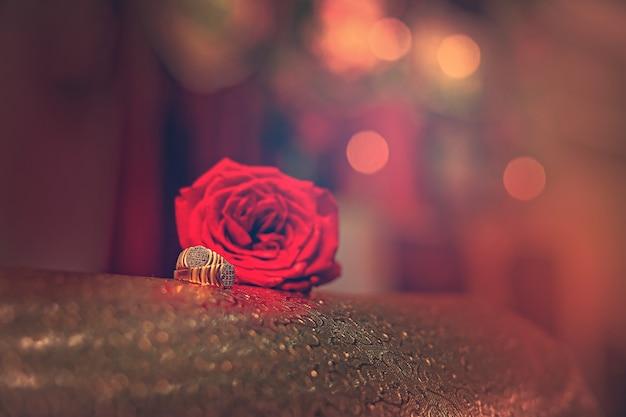 赤いバラの花と黄金の婚約指輪