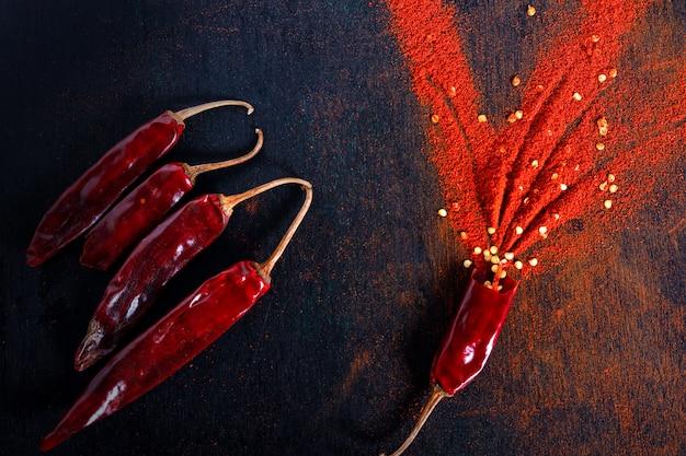 赤唐辛子フレークと黒の背景にチリパウダーバースト