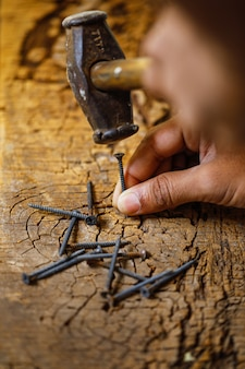 Используя молоток и гвоздь по дереву