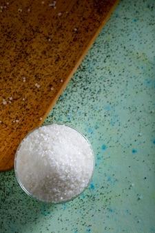 木製の背景にガラスのボウルに砂糖