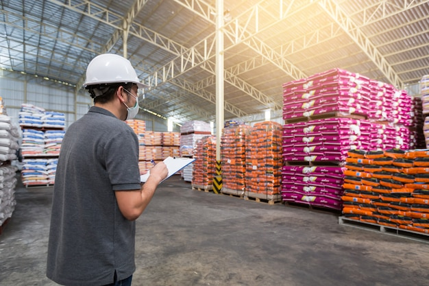 男が倉庫の中で製品の品質をチェックしています。倉庫、品質管理