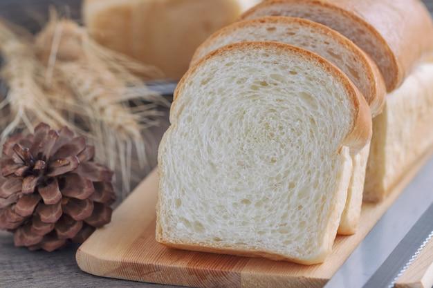 木のまな板の上の柔らかくて粘着性のあるおいしい白パンのスライス