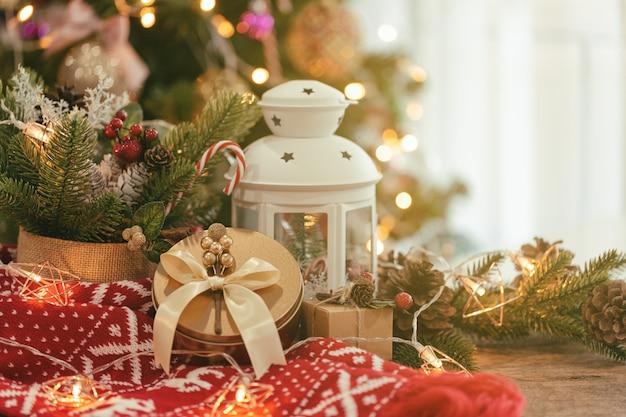 Предпосылка рождественского украшения с листьями и сосновыми шишками, красным шарфом, белым фонарем и подарочной коробкой.
