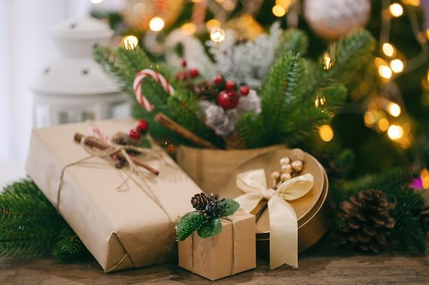 Рождественский фон с подарочной коробкой, сосновыми листьями и сосновыми шишками, белым фонарем и конфетой