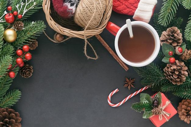 ギフトボックス、松の葉とコーン、ヒイラギのボール、クリスマスのホットチョコレートと黒御影石のテーブル。